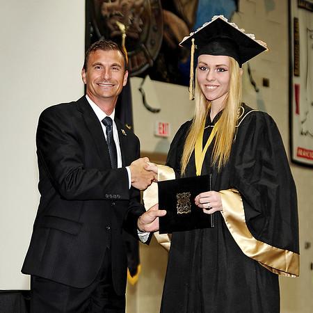 Mark Maynard | for The Herald Bulletin<br /> Dr. Scott Deetz, Superintendent of Madison-Grant Schools, presents Alexis Burton with her diploma at graduation ceremonies.
