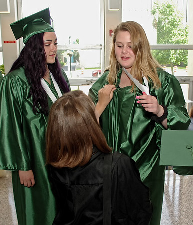 Courtney Kesler helps Lillian Russell don her graduation gown as Carolyn McKinney looks on. (Mark Maynard photo)