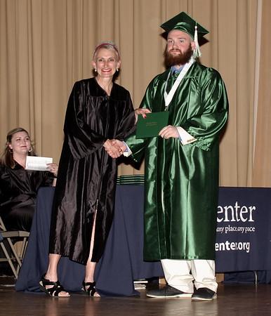 Excel Center Class of 2019 graduate Lee Shepheard accepts his diploma from Carolyn McKinney.  (Mark Maynard photo)