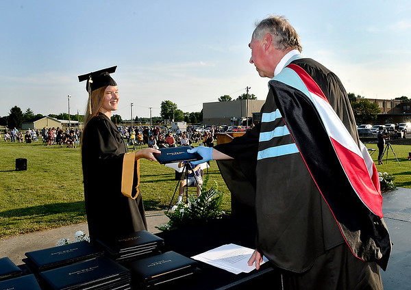 Daleville High School senior Jordan Ashley Cooper receives her diploma from Daleville Schools Superintendent Paul Garrison Wednesday evening during Commencement 2020 held outdoors on the field and track field. 57 seniors received their diplomas.