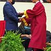 Assistant Principal Tom Jones presents a diploma to a Alexandria Senior.
