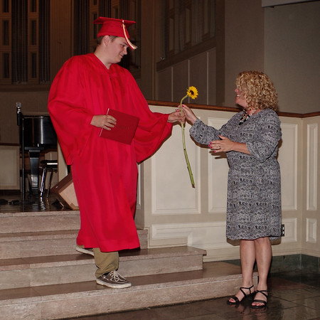 Colton Keesling presents a flower to his mother, Sherri Melton after receiving his diploma during Liberty Christian's commencement exercises.