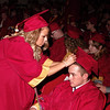 Savannah Cox assists classmate Noah Cothrum with his mortorboard in preparation for graduation ceremonies at Alexandria-Monroe High School.