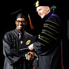Don Knight | The Herald Bulletin<br /> Malik Davis receives his diploma from Anderson University President John Pistole during AU's 100th Commencement on Saturday.