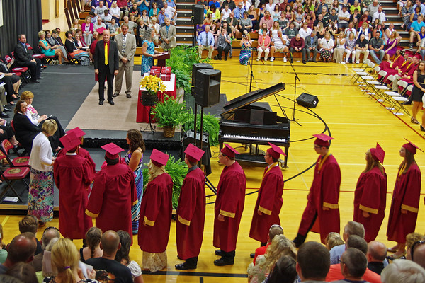 Graduating Alexandria-Monroe High School Seniors prepare to receive their diplomas from School Board President Larry Lipps and Principal Jim Regenold.