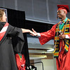 Marc Andrews accepts his diploma from principal Lucinda McCord during Anderson's graduation at the Kardatzke Wellness Center on the campus of Anderson University on Sunday.
