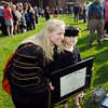 Kelly Rush poses with her daughter Lucy, 5, who is wearing moms cap and holding her framed Doctor of Business Administration degree after AU's commencement was over.