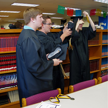 Grant Hoover, Ryan McFeely and Joseph Katzmarek don their caps and gowns in preparation for graduation at Daleville High School.