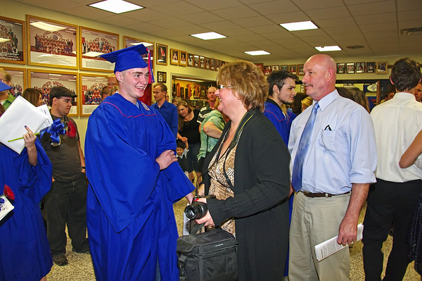 Proud new graduates meet happy friends and family after commencement.