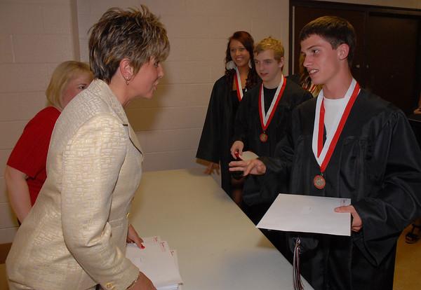 Graduates receive official diplomas following commencement.