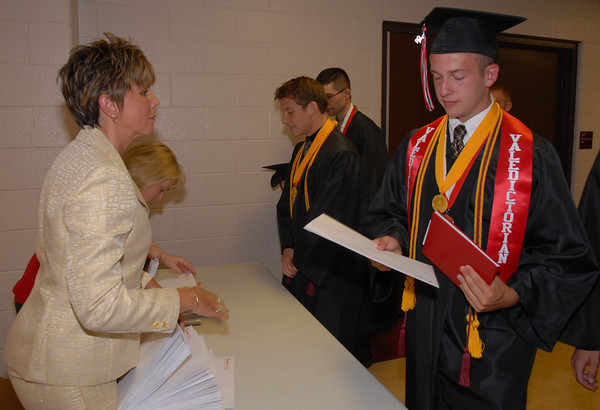 Graduates receive official diplomas following commencement.