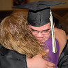 A graduate hugs his mother after commencement.
