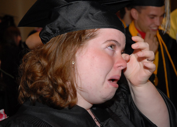 A graduate wipes tears from her eyes after the end of commencement.