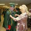 Pendleton Heights High School Auditorium Director Jacque Brown helps Devin Glass with his International Thespian Honor Society braids prior to graduation ceremonies.