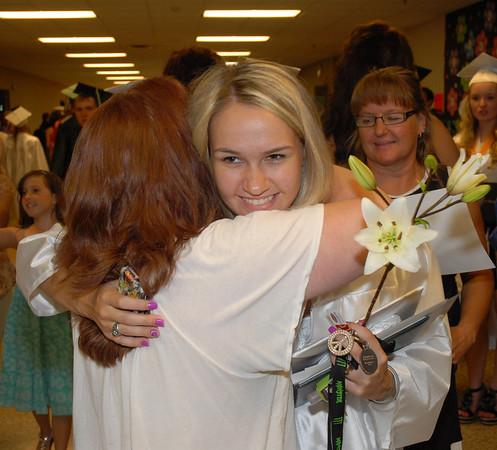 Graduate Shelby Bailey receives a hug from Pendleton Heights world language teacher Janine Taulman