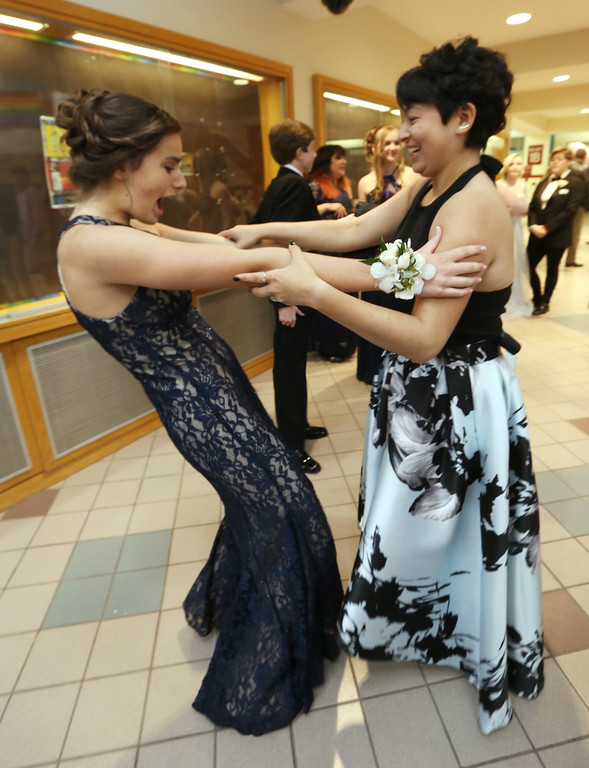. Groton-Dunstable pre-prom gathering at the high school. Carolyn Abraham of Groton, left, greets Willow Chau, allso of Groton. (SUN/Julia Malakie)