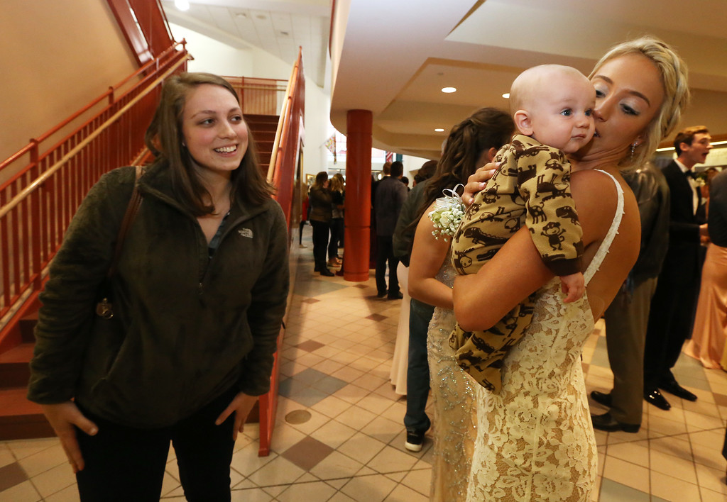 . Groton-Dunstable pre-prom gathering at the high school. Math teacher Kate Lovely of Bedford, N.H., left, looks on as student Olivia Dunsmoor of Pepperell (who goes to GDRHS), holds Ace MacDonald, 5 months old, of Nashua, another teacher\'s baby. (SUN/Julia Malakie)