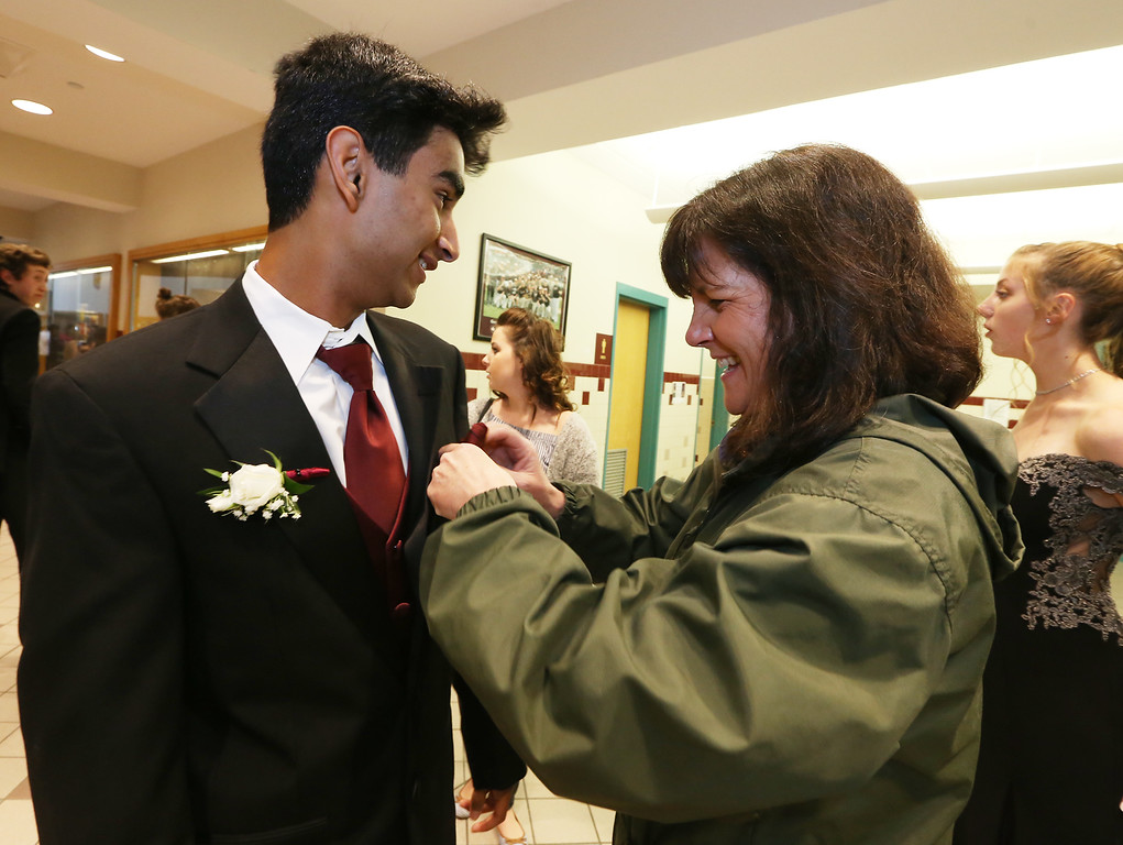 . Groton-Dunstable pre-prom gathering at the high school. Parent Carol Femia of Groton helps Avi Jivanani, also of Groton, with his handkerchief. (SUN/Julia Malakie)