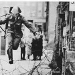 Iconic image of an East German border patrol soldier in full defection,  leaping to freedom in West Berlin as the wall is erected in 1961.