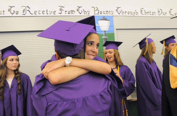 Carolina Gutierrez gives a hug to Robert McCandlish before the Holy Family High School graduation ceremony on Wednesday.<br /> <br /> May 18, 2011<br /> staff photo/David R. Jennings