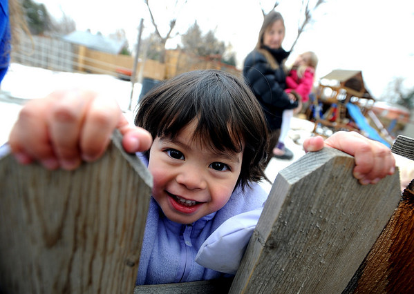 "Sophia Perria, 3, peeks over the fence of the Homestar  Child Development Preschool playground on Thursday. For more photos of the kids, go to  <a href=""http://www.dailycamera.com"">http://www.dailycamera.com</a><br /> <br /> Cliff Grassmick / January 14, 2010"