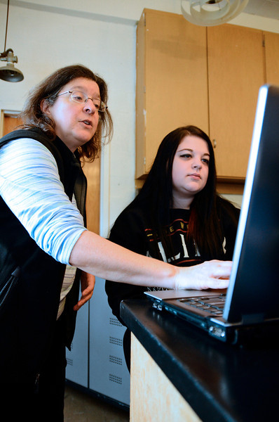 North Central Charter Essential School math and science teacher and math department head, Linda Tarantino, helps junior Alisa Nano, 17, of Fitchburg on a computer programming project on Tuesday as part of Hour of Code, a campaign hosted by Code.org, a non-profit organization that seeks to enhance awareness and growth of computer science in the nation's schools.<br /> SENTINEL & ENTERPRISE / BRETT CRAWFORD