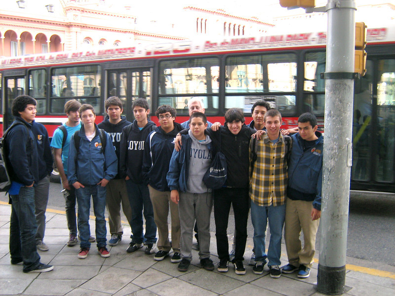 Group photo. Bus obscures the Casa Rosado in background.