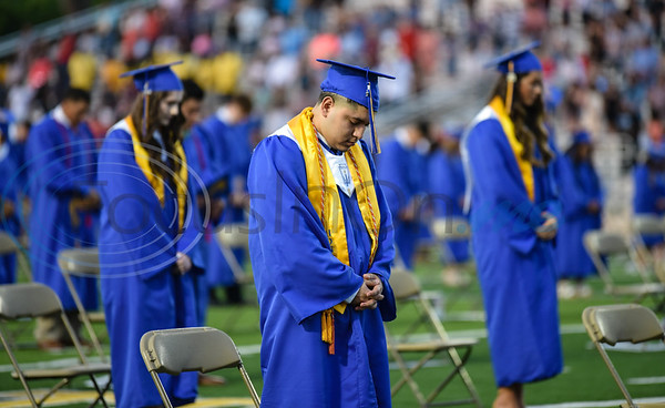 A Jacksonville High School graduate bows his head in prayer at the school's graduation ceremony. The celebration took place at the Tomato Bowl on Tuesday, June 2.