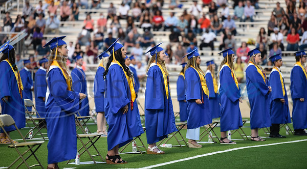 Jacksonville High School seniors stand during their graduation on Tuesday, June 2. 285 students received their diploma at and in-person ceremony at the historic Tomato Bowl.