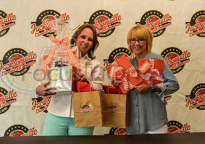 Whataburger franchise Marketing Director Shelly Lipe (left) and Jacksonville Chamber of Commerce President Peggy Renfro (right) smile while holding gifts for Jacksonville Independent School District teachers on Thursday, May 7th before announcing the What-A-Teacher of the Year.