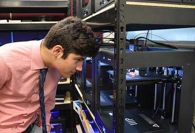 Joey Santana observing a 3-D Printer printing a butterfly