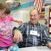 After learning to make a yarn bracelet volunteer Bob Marchetti got some tying it on to his wrist by Johnny Appleseed Elementary School fourth grader Isabelle Keller, 10, on Tuesday at the school. The Johnny Appleseed Elementary School in Leominster has a new program they call Bridges Together. It brings older volunteers in to meet and teach the students some of things they have learned over the years and for the students to show them new stuff. SENTINEL & ENTERPRISE/JOHN LOVE