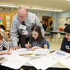 VolunteerJohn Diggins teaches how to balance a check book to Johnny Appleseed Elementary School fourth grader from left Renne Comeau, 9, Abigail Matthews, 10, and Rahim Rashid, 10, on Tuesday at the school. The Johnny Appleseed Elementary School in Leominster has a new program they call Bridges Together. It brings older volunteers in to meet and teach the students some of things they have learned over the years and for the students to show them new stuff. SENTINEL & ENTERPRISE/JOHN LOVE