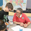 Volunteer Mary Anne Capistrano learns how to make a paper cube from Johnny Appleseed Elementary School fourth grader Matt Dietz, 10, on Tuesday at the school. The Johnny Appleseed Elementary School in Leominster has a new program they call Bridges Together. It brings older volunteers in to meet and teach the students some of things they have learned over the years and for the students to show them new stuff. SENTINEL & ENTERPRISE/JOHN LOVE