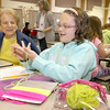 Volunteer Louise Lenno listens to Johnny Appleseed Elementary School fourth grader Roslyn Perry, 10, as she teachers how to finger knit. The Johnny Appleseed Elementary School in Leominster has a new program they call Bridges Together. It brings older volunteers in to meet and teach the students some of things they have learned over the years and for the students to show them new stuff. SENTINEL & ENTERPRISE/JOHN LOVE