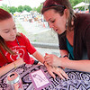 Gina Russo, a student at Sky View Middle School, gets a henna tattoo by Mandy Roberge during the Johnny Appleseed Lawn Party in Leominster on Saturday afternoon. Funds raised during the event go towards student activities throughout the year. SENTINEL & ENTERPRISE / Ashley Green