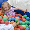 Grace Kneeland, 4, plays in the ball pit during the Johnny Appleseed Lawn Party in Leominster on Saturday afternoon. Funds raised during the event go towards student activities throughout the year. SENTINEL & ENTERPRISE / Ashley Green