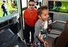 Five-year-old kindergartner Landon Boniface boards a school bus on K Day with his father James.   Thursday, August 7, 2014.   Photo by Geoff Patton