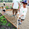 Zachary Smerdell, right, works with InColor's Kyle Hechard on watering a garden plot as part of a group of 4th graders Kohl Elementary School in Broomfield planting a garden behind the school as part of Disney's Planet Challenge, an environmental and science competition for grades 3-8. Andrew Carroll, left, helps by holding the hose. May 22, 2012<br /> Photo by Paul Aiken