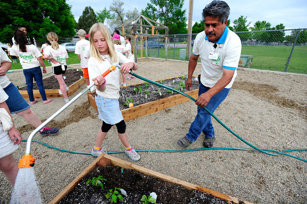Tautum Roque waters with the help of InColor volunteer Gerardo Rodriguez as part of a group of 4th graders from Kohl Elementary School in Broomfield planting a garden behind the school as part of Disney's Planet Challenge, an environmental and science competition for grades 3-8. May 22, 2012<br /> Photo by Paul Aiken