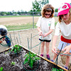 Julia Kirk, at left and Hope Harper-Hanak cage peppers as part of a group of 4th graders from Kohl Elementary School in Broomfield planting a garden behind the school as part of Disney's Planet Challenge, an environmental and science competition for grades 3-8. May 22, 2012<br /> Photo by Paul Aiken
