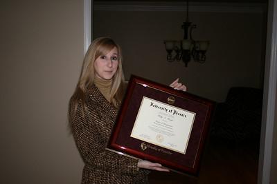 Kelly holding her degree newly framed.