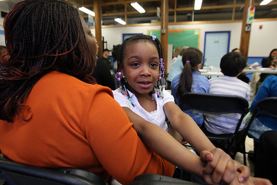 Board of Trustees meeting of the Lowell Community Charter Public School. Parents and staff show up in force, mostly in support of head of school Kathy Egmont. Martine Megnigbeto, with her daughter Mira Sebastiao, 6, a 1st grader at LCCPS, listens to the discussion. (SUN/Julia Malakie)