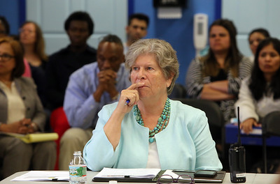 Board of Trustees meeting of the Lowell Community Charter Public School. Parents and staff show up in force, mostly in support of head of school Kathy Egmont. Kathy Egmont listens to a supportive speaker. (SUN/Julia Malakie)