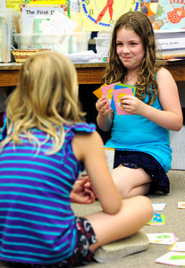 Lilah Blackburn, right, hopes to stump classmate Madeline Forney in the game of rhyming GO FISH during the 2nd graders work on rhyming words in the literacy portion of the day's curriculum in Brieda Gessaman's class at Whittier Elementary on Tuesday  May 22, 2012. For more photos go to www.dailycamera.com Photo by Paul Aiken