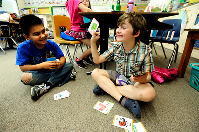 James Gerrity is happy with his answer during a game of rhyming GO FISH as David Plascencia Galvan, left,  waits his turn during the 2nd graders work on rhyming words in the literacy portion of the day's curriculum in Brieda Gessaman's class at Whittier Elementary on Tuesday  May 22, 2012. For more photos go to www.dailycamera.com Photo by Paul Aiken  Brieda Gessaman