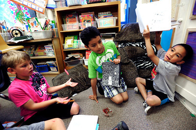 Jose Perla-Marinez, at right, shows off his work as Thoe Sustronk, left and Alan Rivera work together during the 2nd graders work on rhyming words in the literacy portion of the day's curriculum in Brieda Gessaman's class at Whittier Elementary on Tuesday  May 22, 2012. The group was working on stories and plays together. For more photos go to www.dailycamera.com Photo by Paul Aiken