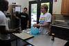 Students Makitu Makori, Jon Gonzalez, and Spencer Hambleton prepare butter cookies using the utility center island at the new Leahy House kitchen.