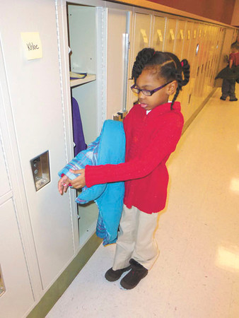 Debbie Wachter/NEWS<br /> Kindergarten student Talia Lewis takes off her coat at her new locker at Lockley. The students said they are excited to have lockers for the first time in their new school.