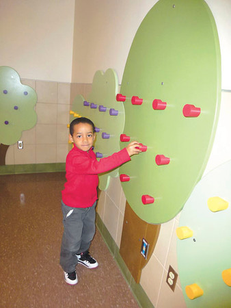 Debbie Wachter/NEWS<br /> Lockley kindergarten student Will Pickney pretends he is picking an apple from a tree in the cafeteria. The wooden trees line the cafeteria walls, and the fruit on them are actually pegs for the children to hang their coats on during breakfast.